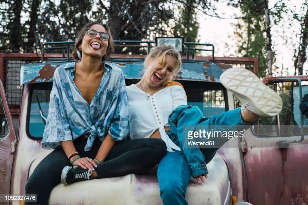 friends sitting on a broken truck, having fun - donner un coup de pied photos et images de collection
