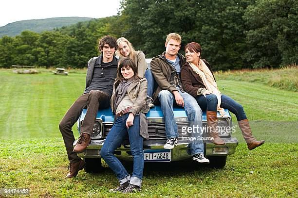 Friends sitting on a car