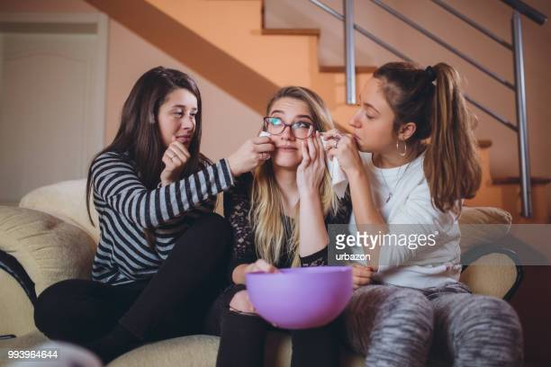 friends sitting on a couch watching movies - girlfriends films stock pictures, royalty-free photos & images