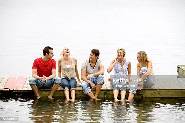 Friends sitting on a jetty by the water Ljustero Stockholm archipelago Sweden.