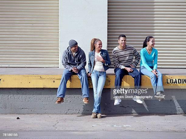 Friends sitting on a loading dock