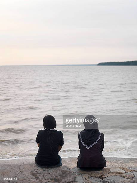 friends sitting on a seawall near the muar river. - seawall stock pictures, royalty-free photos & images