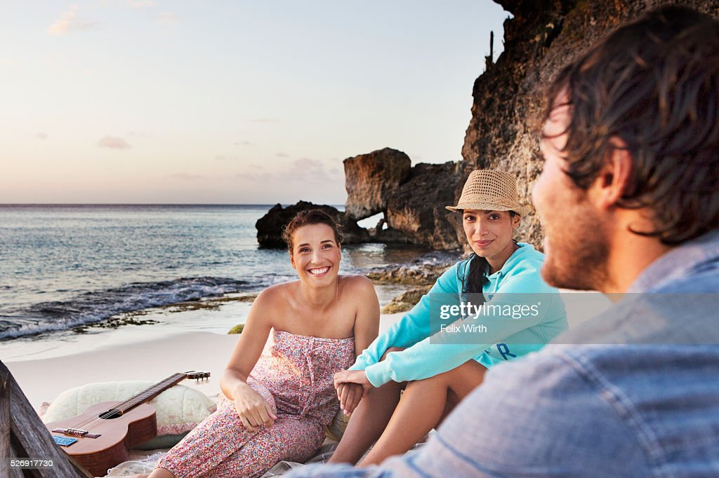 Friends sitting on beach at dusk : Foto stock