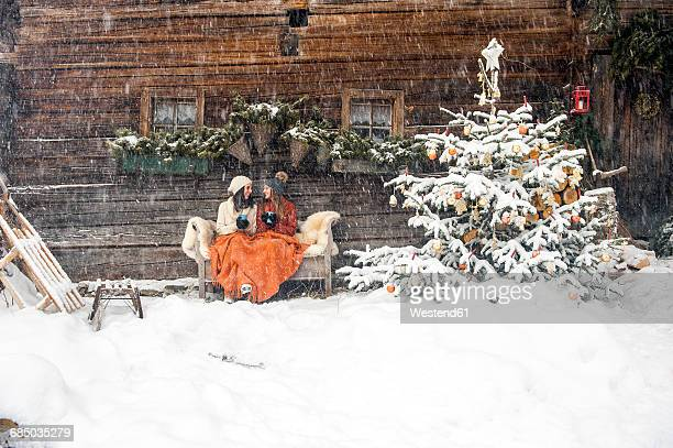 Friends sitting on bench by Christmas tree in front of mountain hut