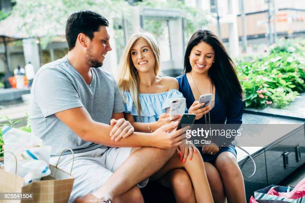 Friends sitting on bench texting on cell phones