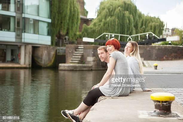 Friends sitting on canal side, East London, UK
