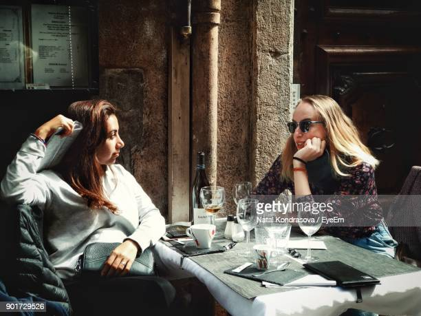 friends sitting on chairs at sidewalk cafe - french cafe stock photos and pictures