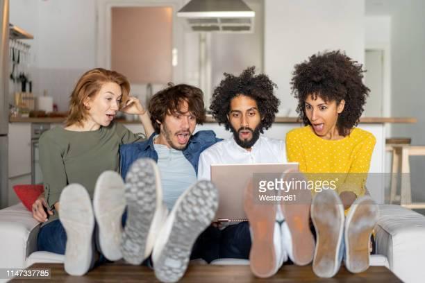 friends sitting on couch, watching laptop - seulement des adultes photos et images de collection
