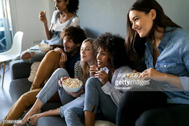 friends sitting on couch watching tv - anticipation stock pictures, royalty-free photos & images