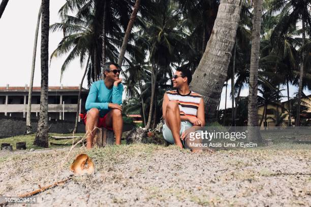 Friends Sitting On Field Against Palm Trees