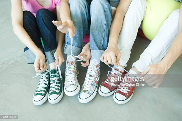 friends sitting on floor, wearing canvas shoes, tying laces, low section - tying shoelace stock pictures, royalty-free photos & images