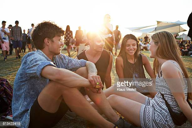 Friends sitting on grass at sunset