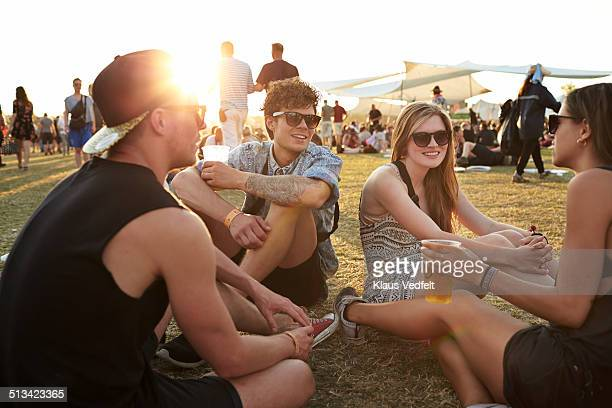 Friends sitting on grass, drinking beer