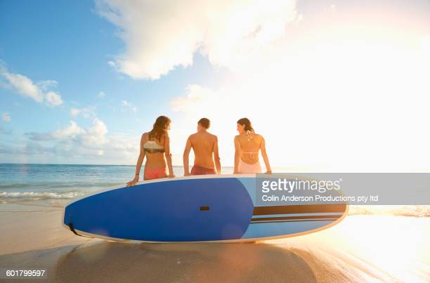 Friends sitting on paddle boards on beach