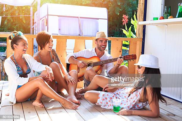 Friends sitting on pavilion and playing guitar