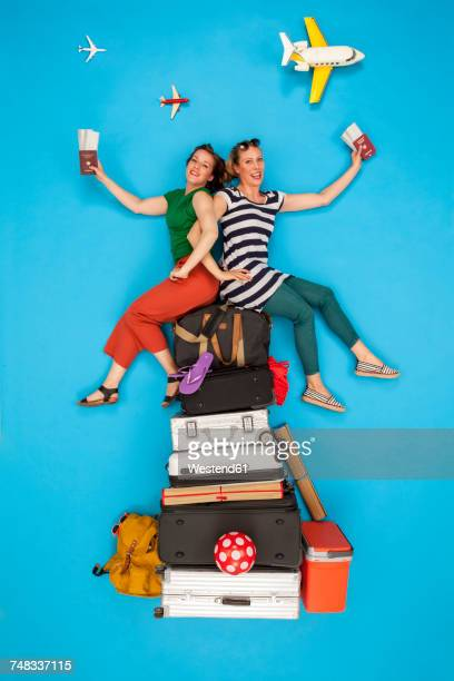 Friends sitting on pile of luggage waiting for departure, holding passports and tickets