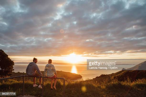 friends sitting on railing against sky during sunset - new zealand stock pictures, royalty-free photos & images