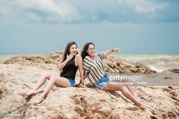 friends sitting on rock by sea against sky - ruben vardanyan stock pictures, royalty-free photos & images