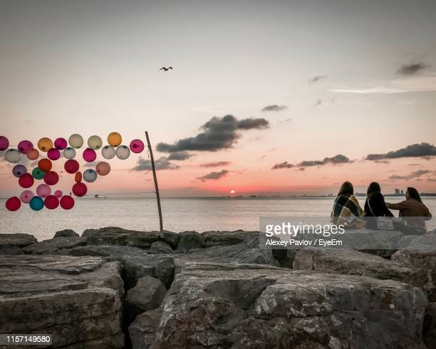 friends sitting on rocks by sea against sky during sunset - kadikoy stock photos and pictures