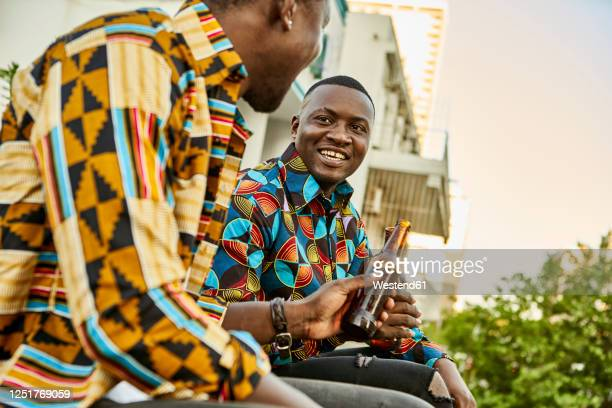 friends sitting on roof terrace in the city drinking beer, maputo, mozambique - mozambique stock pictures, royalty-free photos & images