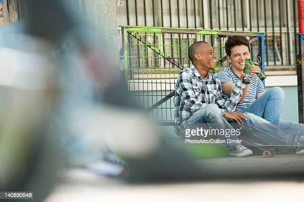 Friends sitting on sidewalk toasting