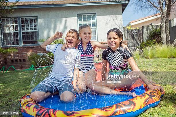 Friends sitting on slip 'n slide in yard