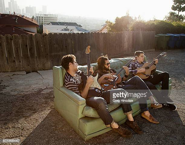 Friends sitting on sofa in backyard playing guitars