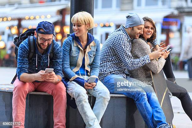 Friends sitting on street and having fun