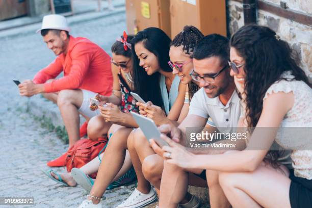 Friends sitting on street and using smart phones