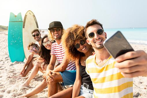 Friends sitting on the beach, having fun, taking selfies - gettyimageskorea