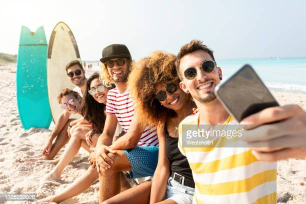 friends sitting on the beach, having fun, taking selfies - beach fun stock pictures, royalty-free photos & images