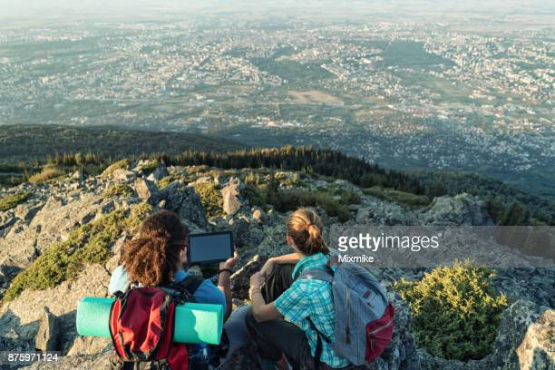 Friends sitting on the mountain peak and holding tablet