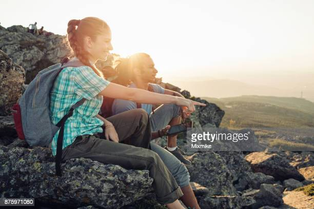 Friends sitting on the mountain peak relaxing and holding tablet