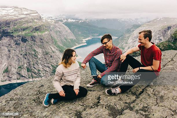 Friends sitting on the Trolltunga