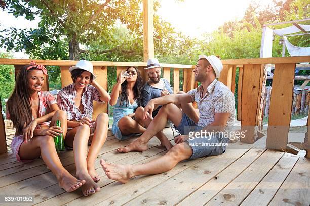 friends sitting on veranda and drinking beer - casita de campo fotografías e imágenes de stock