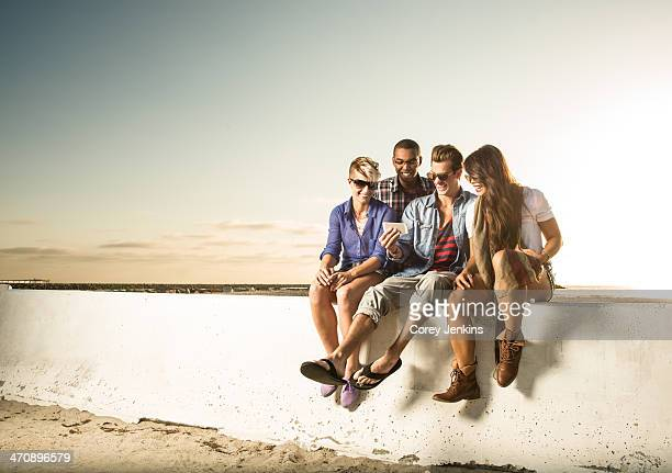 Friends sitting on wall with smartphone, Mission Beach, San Diego, California, USA