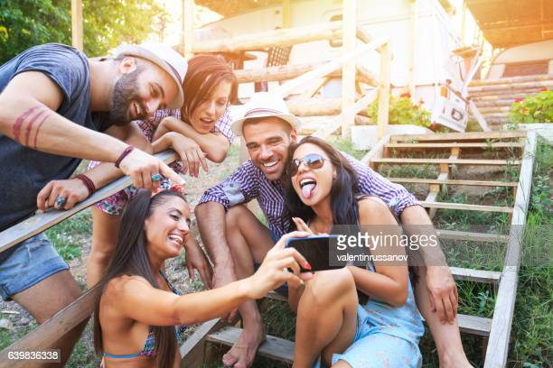 Friends sitting on wooden stairs and making selfie