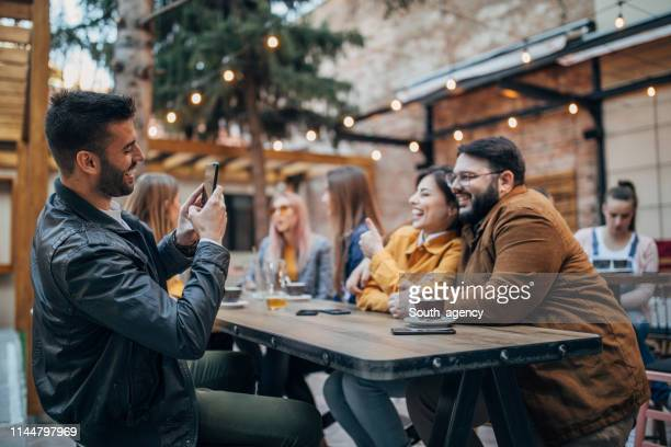 friends sitting outdoors in cafe - pavement cafe stock pictures, royalty-free photos & images