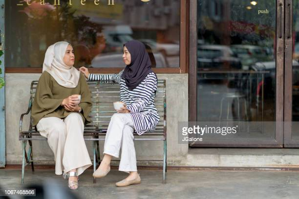 Friends sitting outside a cafe talking