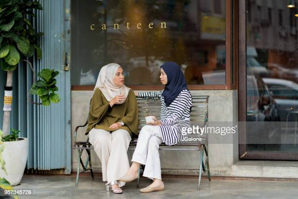 friends sitting outside drinking coffee and chatting - malay stock photos and pictures