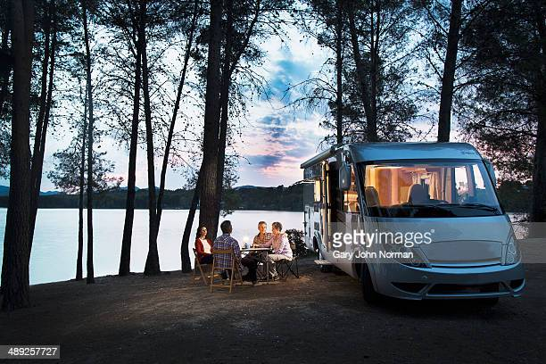friends sitting outside motorhome in the evening - norman elder stock photos and pictures