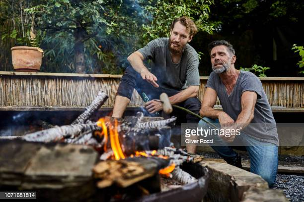 friends sitting together at camp fire roasting sausages - lagerfeuer stock-fotos und bilder
