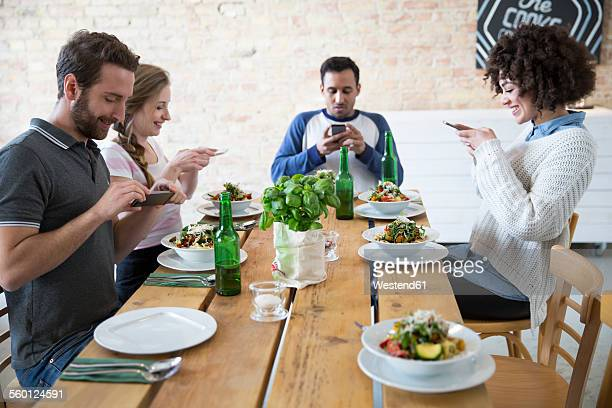 Friends sitting together at dining table posting food