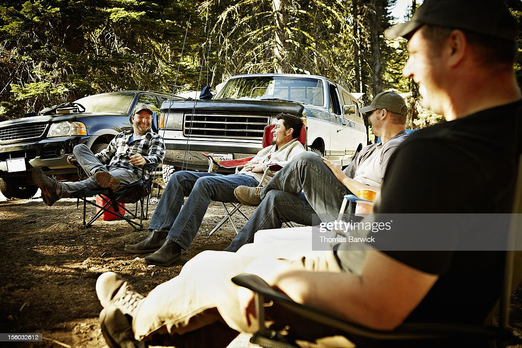 Friends sitting together at hunting camp laughing : Stock Photo