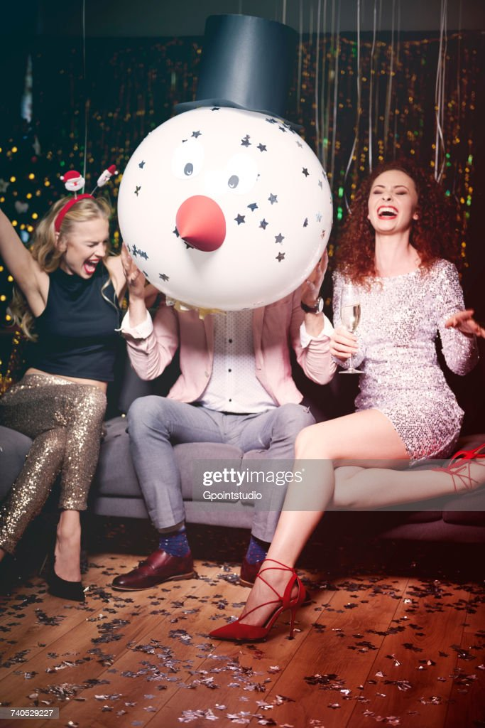 Friends sitting together at party, man holding snowman head in front of face, women laughing : Stock Photo