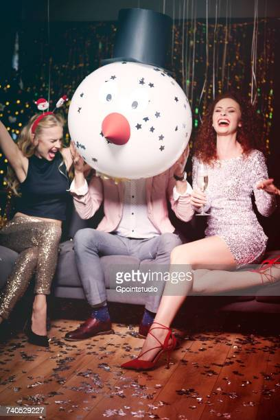 friends sitting together at party, man holding snowman head in front of face, women laughing - santa face stockfoto's en -beelden