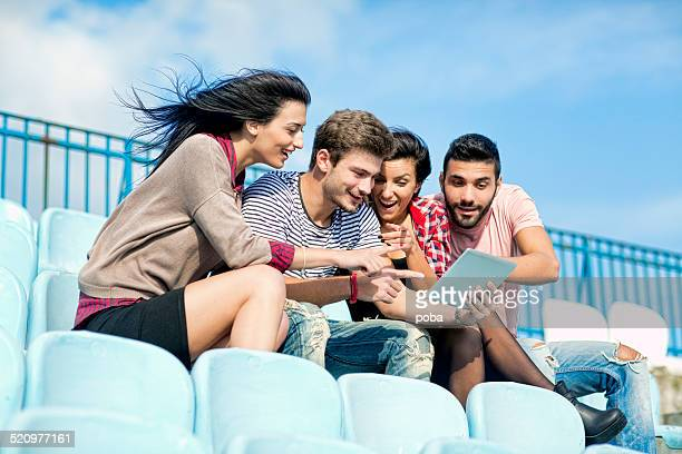 friends sitting together on the bleachers and  using digital tablet