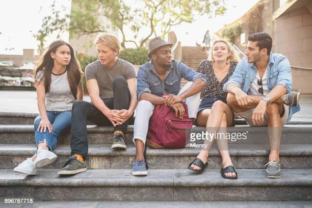 Friends sitting together talking in Darling Harbour Sydney
