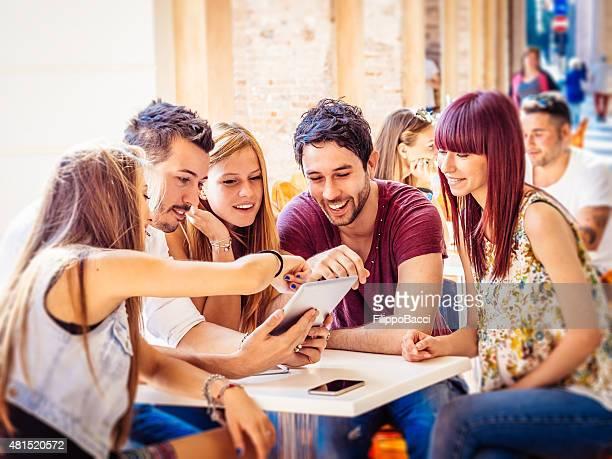Freunde sitzen zusammen mit Tablet