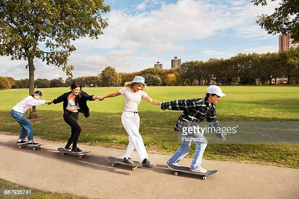Friends skateboarding in a park